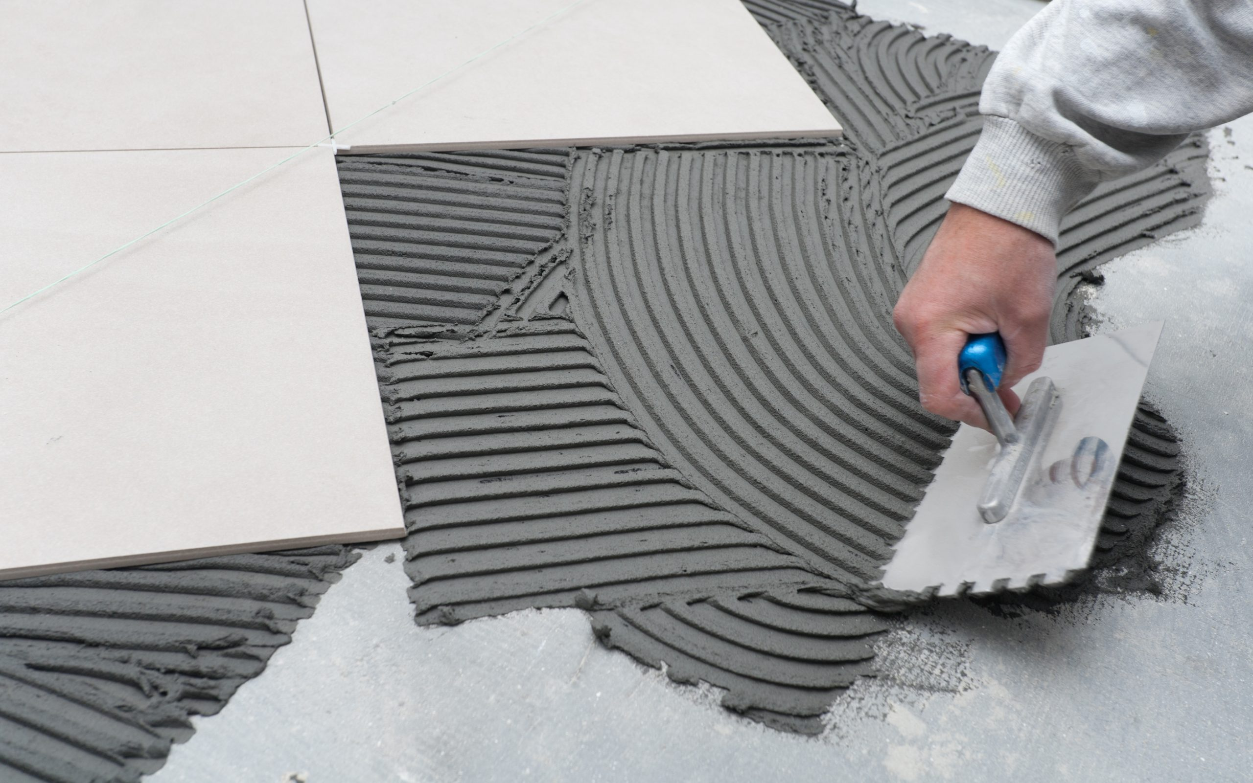 Spreading wet mortar before applying tiles on bathroom floor.