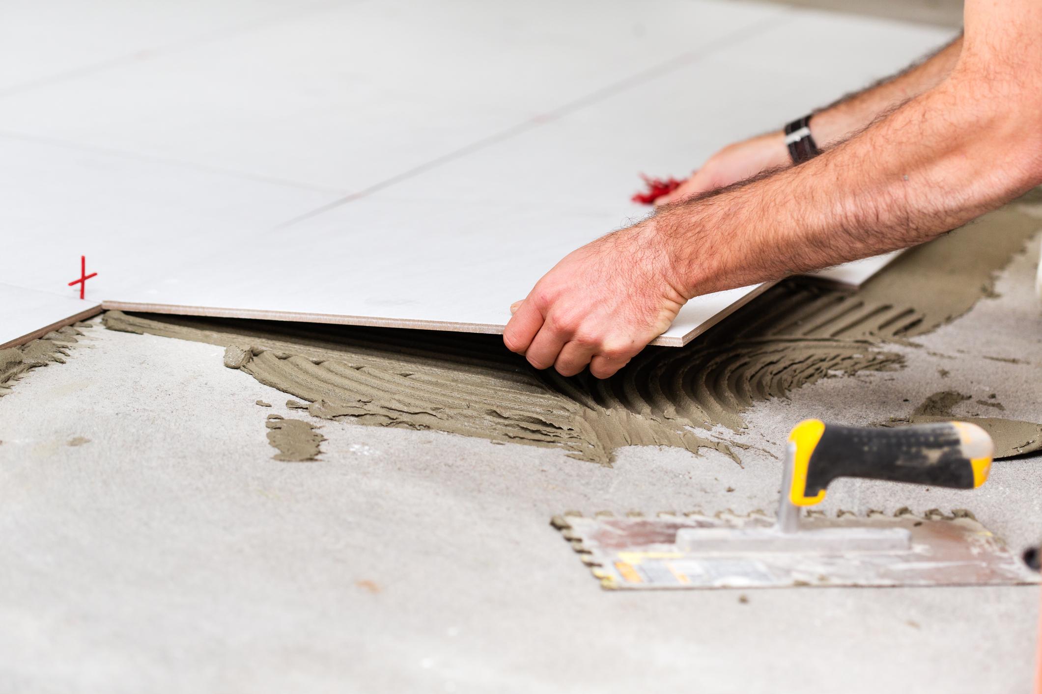 Home improvement - Worker installing tiles